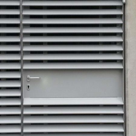 In Beschattungssystem integrierte Tür aus C100 Easyfix Lamellen, ausgeführt für die Firma Miba.