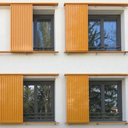 Schiebeläden mit Lamellen-Füllung als Sonnenschutz an der Fassade der Wohnhaus-Anlage Utendorfgasse in Wien, ausgeführt von der Firma Linzner.