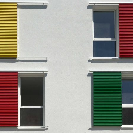 Schiebelaeden mit Lamellen-Fuellung als Sonnenschutz an einer Fassade in Liechtenberg, ausgefuehrt von der Firma Linzner.