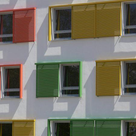 Schiebelaeden mit Lamellen-Fuellung als Sonnenschutz an der Fassade des Jufa Gaestahaus Wien, ausgefuehrt von der Firma Linzner.